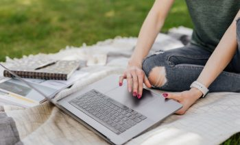 anonymous-lady-using-laptop-for-studies-in-sunny-park-4497759